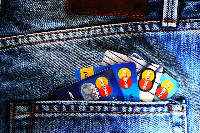 Credit cards peeking out of a jeans pocket.